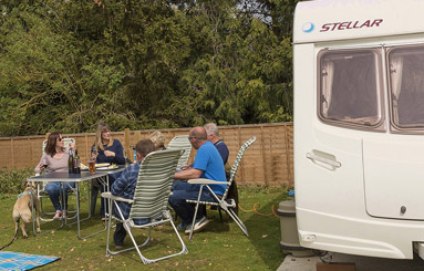 people having a drink outside their caravan at the Five Bells